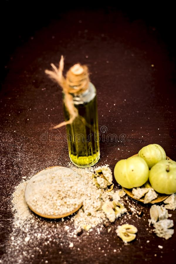 Raw fresh ripe Phyllanthus emblica,amla or Indian gooseberry with its powder and extracted oil on wooden surface. royalty free stock photography
