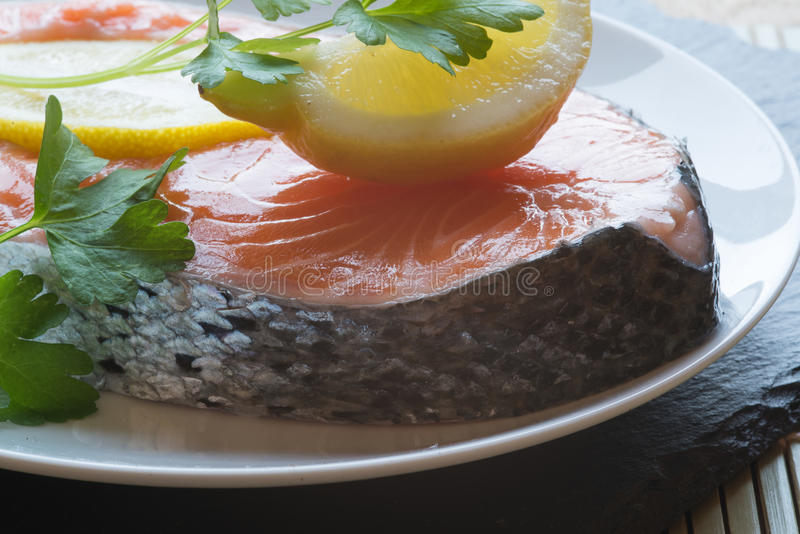 Raw fresh salmon cutlet steak with lemon and parsley garnish stock photography