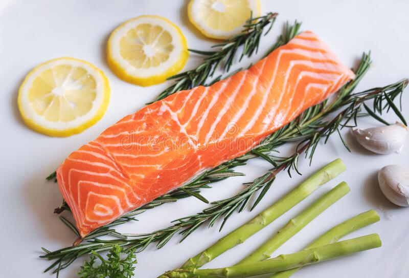 Raw fresh salmon fillet with herbs and ingredients, in white dish stock photos