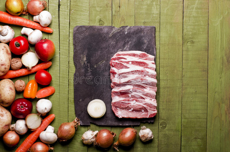 Raw frozen meat on green wooden background. Pork neck raw, vegetables close-up on a slate board. Copy space. royalty free stock images