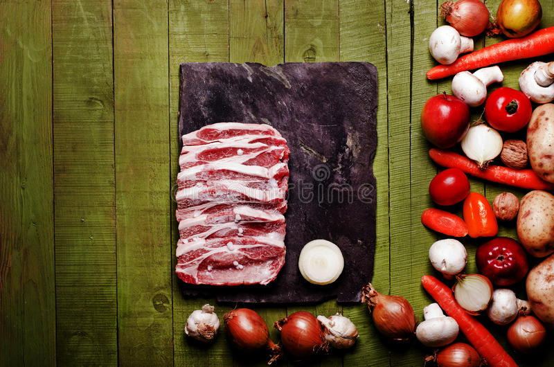 Raw frozen meat on green wooden background. Pork neck raw, vegetables close-up on a slate board. Copy space. Raw frozen meat on green wooden background. Pork royalty free stock photo