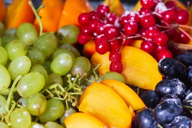 Raw fruits berries platter, mango, oranges, kiwi strawberries, blueberries grapefruit grapes, bananas apples on the white plate,. On the off white table, top royalty free stock image