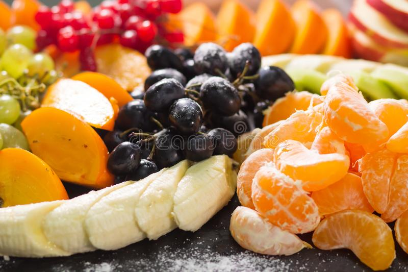 Raw fruits berries platter, mango, oranges, kiwi strawberries, blueberries grapefruit grapes, bananas apples on the white plate,. On the off white table, top stock images