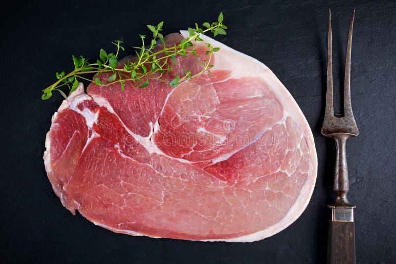 Raw gammon steak on black stone background stock images
