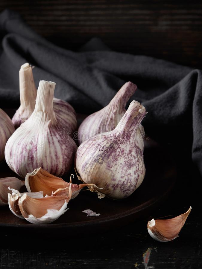 Raw garlic on black. Garlic cloves and bulbs on black stock photos