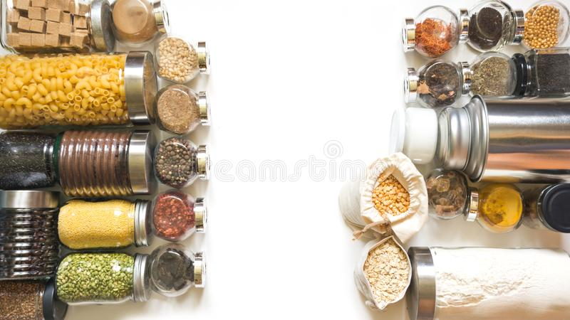 Raw grains, cereals and pasta in glass jars on white table. Healthy cooking, clean eating, zero waste concept. Balanced food. royalty free stock image