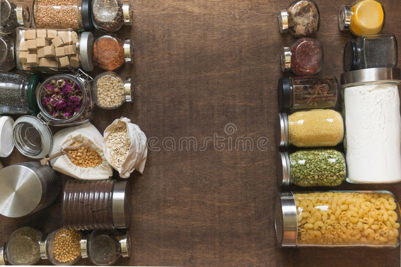 Raw grains, cereals and pasta in glass jars on wooden table. Healthy cooking, clean eating, zero waste concept. Balanced dieting. Raw grains, cereals and pasta stock image