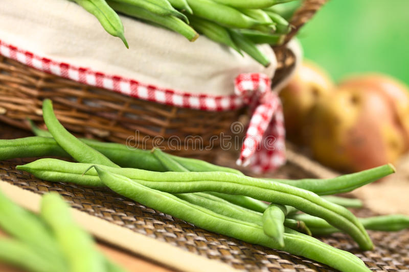 Raw Green Beans. Fresh raw green beans in front of a basket with potatoes in the back (Selective Focus, Focus on the long bean one third into the image stock images
