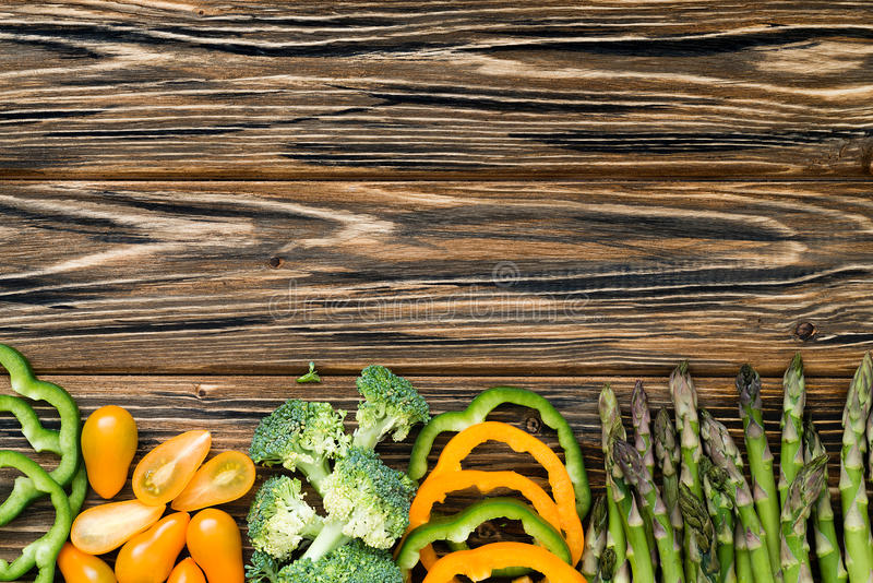Raw green and yellow veggies. Flat lay on wooden table royalty free stock photos