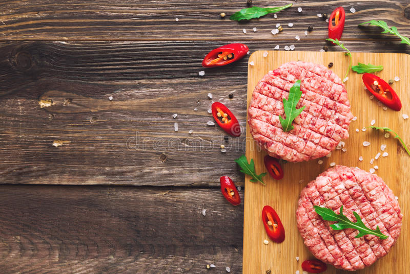 Raw ground beef burgers. With chili pepper and arugula on rustic wooden background. Top view stock image