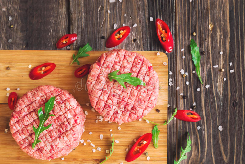 Raw ground beef burgers. With chili pepper and arugula on rustic wooden background. Top view stock photo