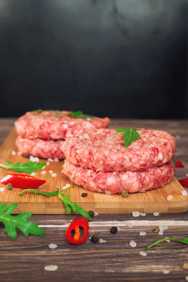 Raw ground beef burgers. With chili pepper and arugula on rustic wooden table. Selective focus royalty free stock images