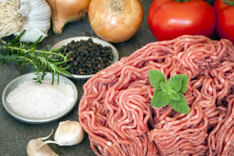 Raw Ground Beef and Ingredients. Raw ground beef with tomatoes, onions, garlic, rosemary, salt and pepper stock photo