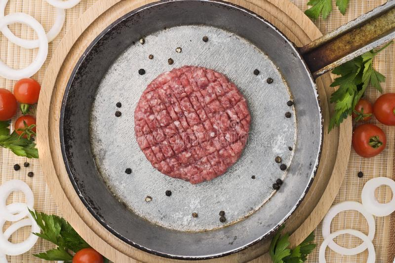 Raw Ground beef meat Burger steak cutlets in a cast iron pan on a wooden background. Burger with vegetables and spices royalty free stock photos