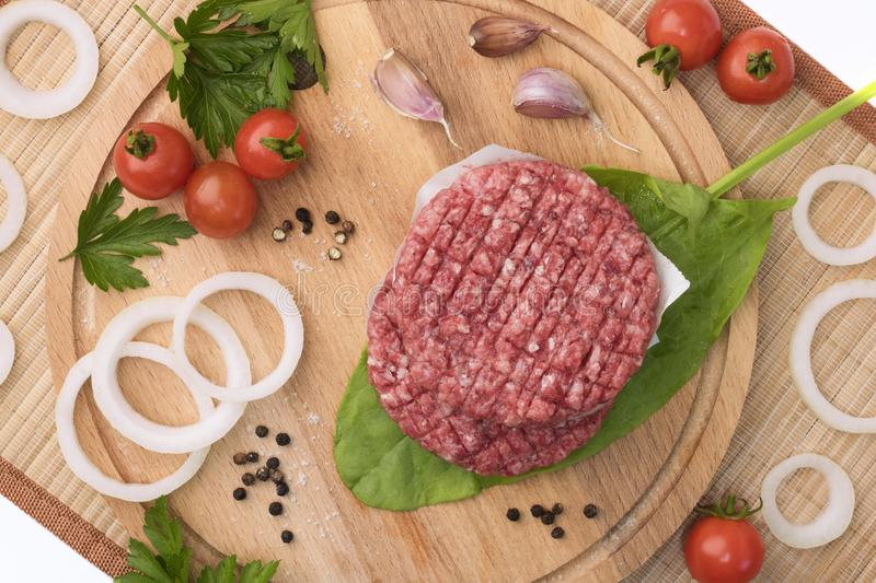 Raw Ground beef meat Burger steak cutlets on a wooden board background. Cutlet for burger with vegetables and spices stock images