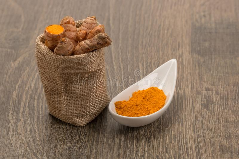 Raw and ground turmeric, royalty free stock photo