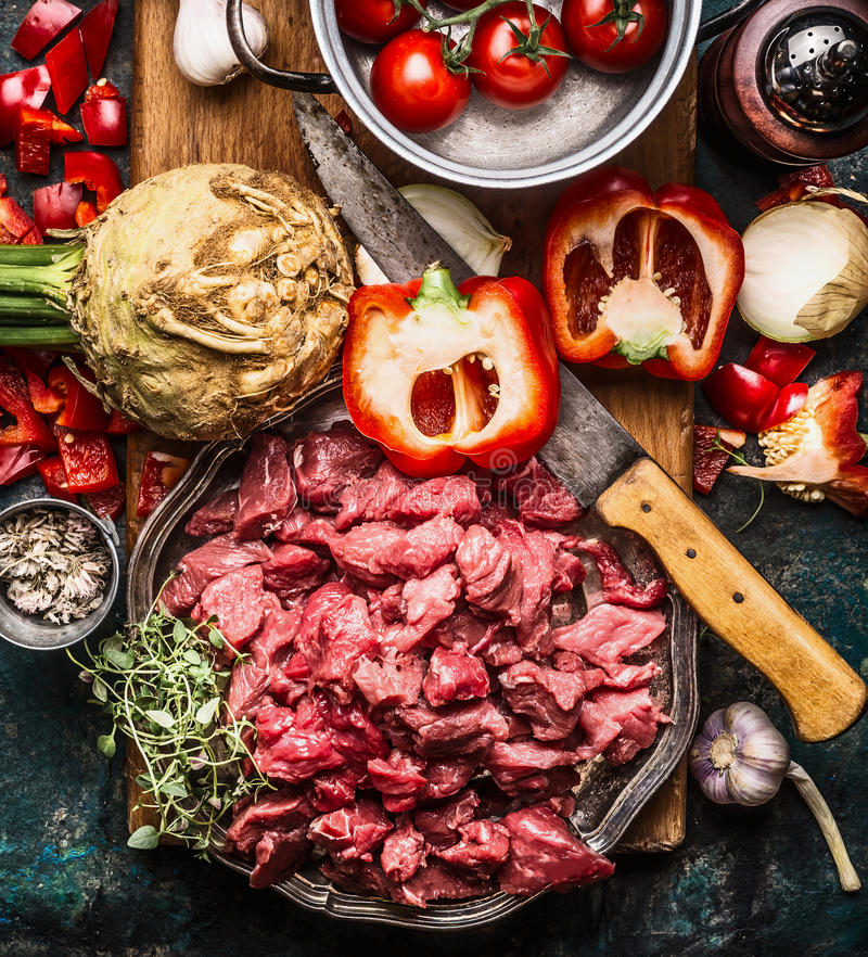 Raw gut meat with kitchen knife fresh vegetables, seasoning and spices for tasty cooking on dark rustic background. Top view stock image