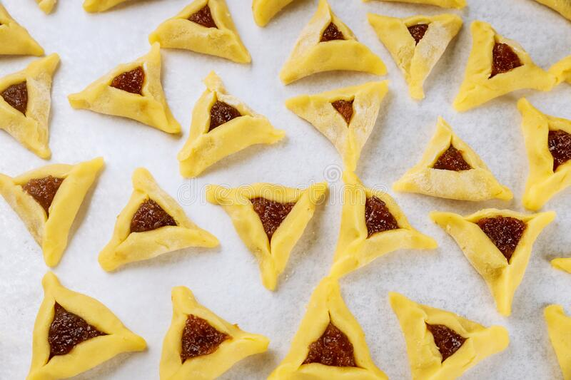 Raw hamantaschen jewish cookies with jam on oven tray stock photos