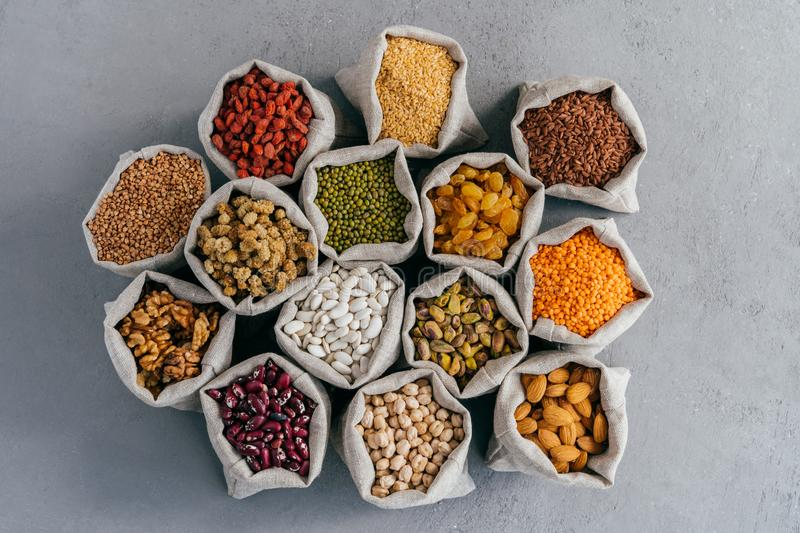 Raw healthy grain food and legume. Hessian bags of cereals and dried fruit. Packing groats at market against grey background royalty free stock photo