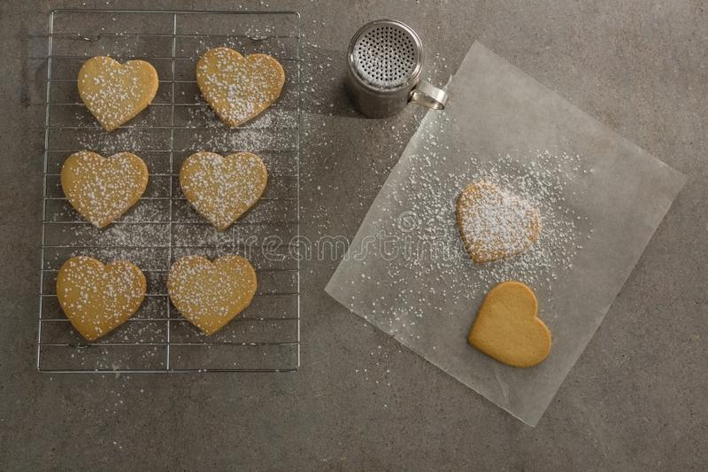 Raw heart shape cookies on baking tray with flour shaker strainer and wax paper stock images