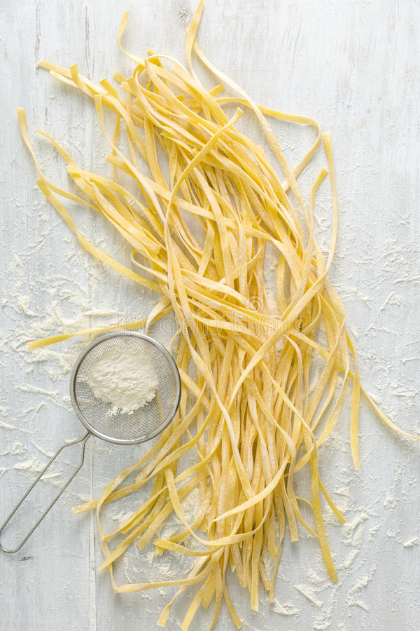 Raw homemade noodles with flour sieves on white wooden table. Raw homemade noodles with flour sieves on white rustic wooden table, top view stock photos