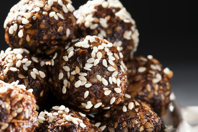 Raw homemade paleo energy balls with rolled oats, nuts, dates and sesame, horizontal, close up. Vegan sweet dessert royalty free stock photos