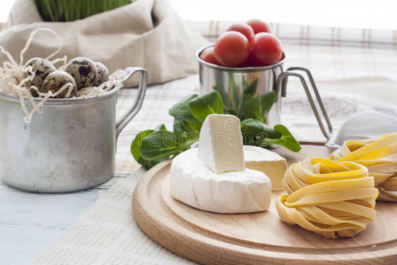 Raw homemade pasta, quail easter eggs in a aluminum cup, green lettuce, tomatoes and flour on wooden table royalty free stock images