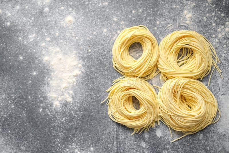 Raw homemade spaghetti nest with flour on a grey background royalty free stock photos