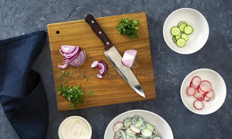 Raw ingredients cooking of summer healthy vegetable salad dark stone surface, top view stock photography