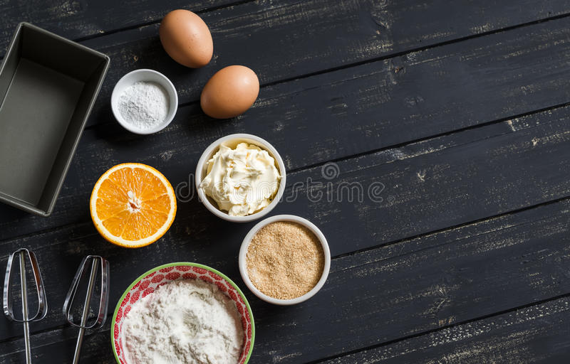 Raw ingredients - flour, eggs, butter, sugar, orange - to cook orange cake. Ingredients for baking. Ingredients for the dough. On a dark wooden surface royalty free stock photography