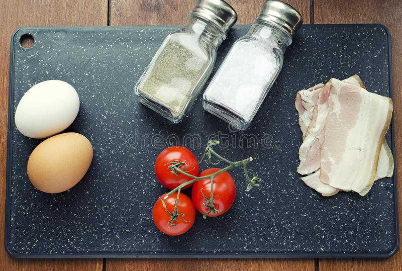 Raw ingredients for scrambled eggs, fresh formula, eggs bacon tomatoes salt and pepper on the cutting board top view stock photography