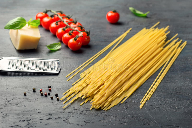 Raw Italian spaghetti with ingredients for cooking classic Italian pasta royalty free stock photography