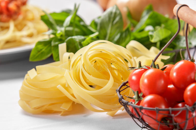 Raw italian tagliatelle pasta and cherry tomatoes royalty free stock images