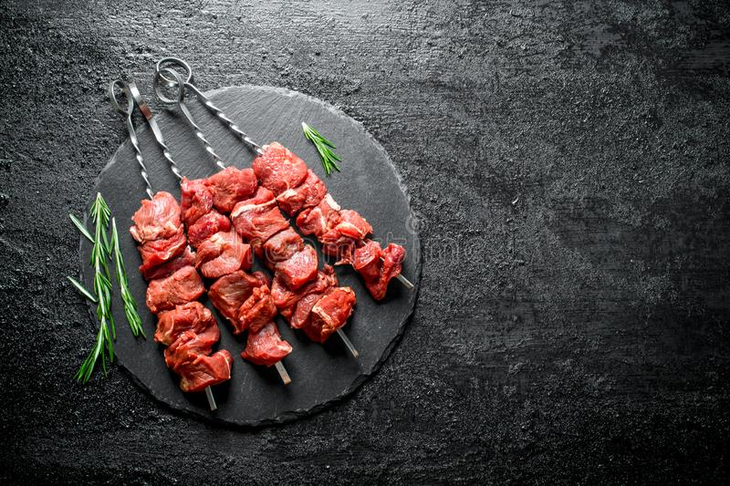 Raw kebab with rosemary. On black rustic background stock photos