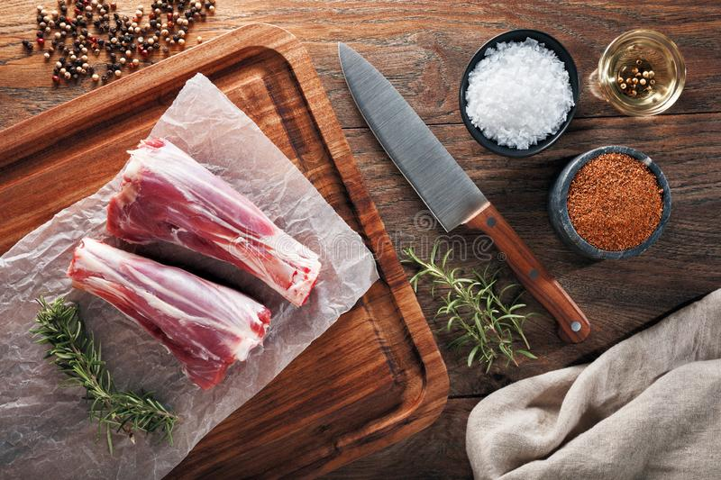 Raw lamb drumstick on white cooking paper and wooden cutting table. Decorated with herbs, spices, chef`s knife and napkin. Raw lamb drumstick on white cooking royalty free stock images