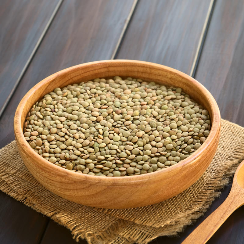 Raw Lentils. (lat. Lens culinaris) in wooden bowl, photographed on dark wood with natural light (Selective Focus, Focus one third into the royalty free stock photo