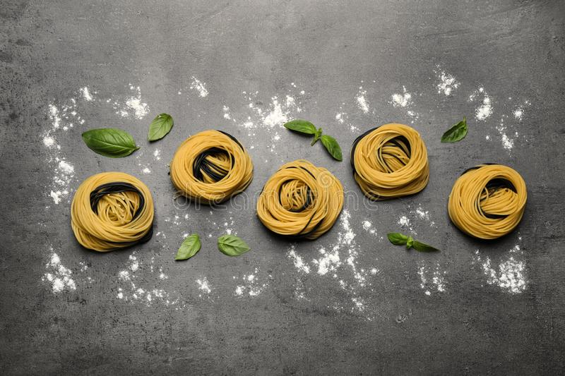 Raw linguine pasta with basil on grey table, flat lay royalty free stock photos