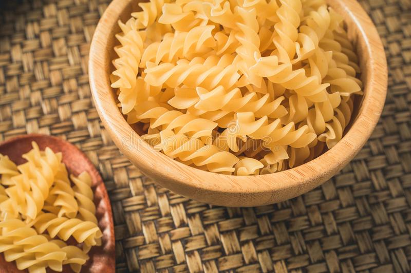 Raw macaroni in a bowl and ladle wood. royalty free stock photo