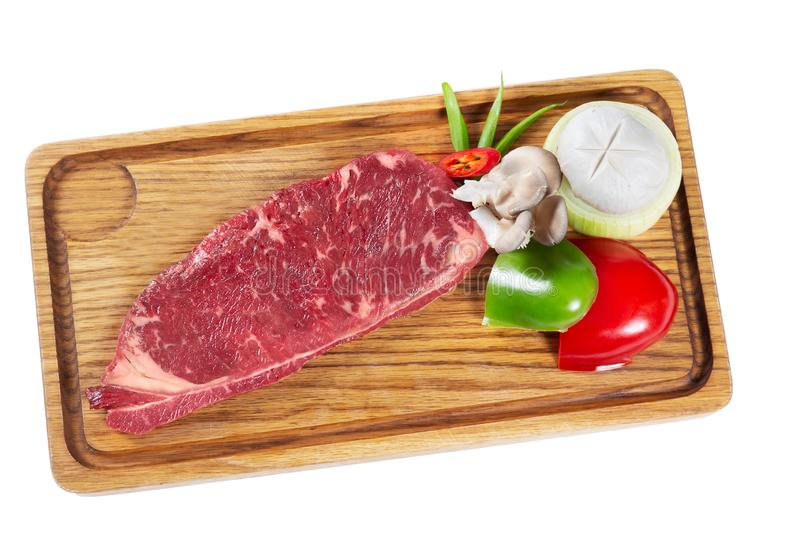 Raw marble meat steak with vegetables on wooden desk isolated on white stock images