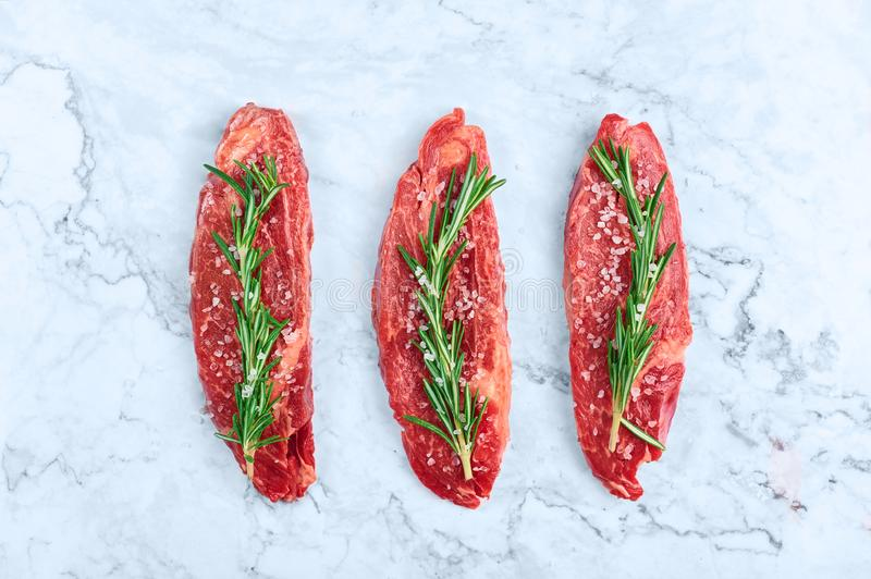 Raw marbled beef steaks with green rosemary branch and sea salt at white marble background royalty free stock photography