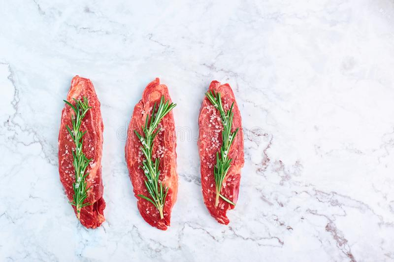 Raw marbled beef steaks with green rosemary branch and sea salt at white marble background stock photos
