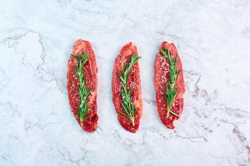 Raw marbled beef steaks with green rosemary branch and sea salt at white marble background royalty free stock image