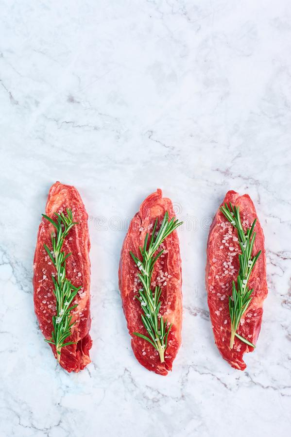 Raw marbled beef steaks with green rosemary branch and sea salt at white marble background stock photography
