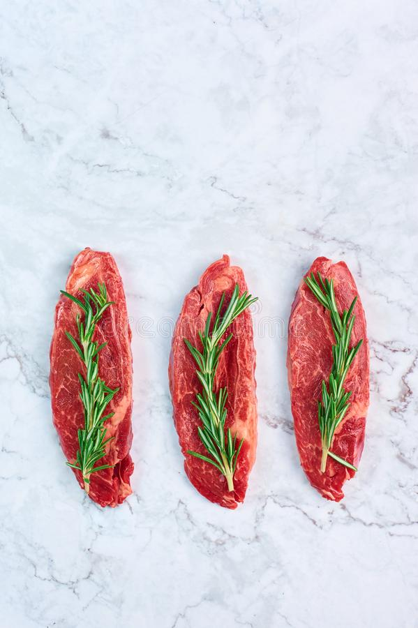 Raw marbled beef steaks with green rosemary branch at white marble background stock images