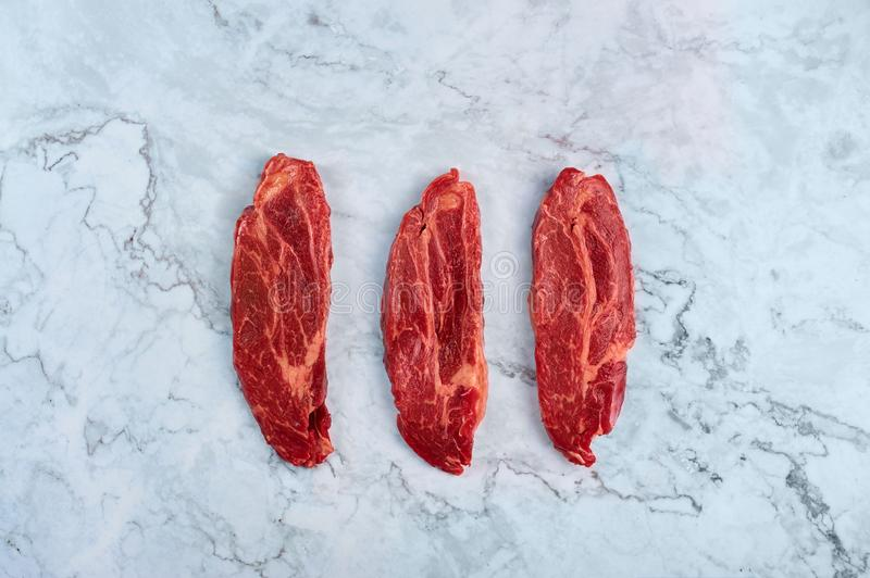 Raw marbled beef steaks at white marble background royalty free stock photos