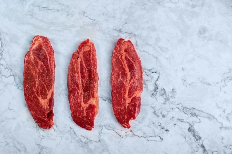 Raw marbled beef steaks at white marble background stock photos