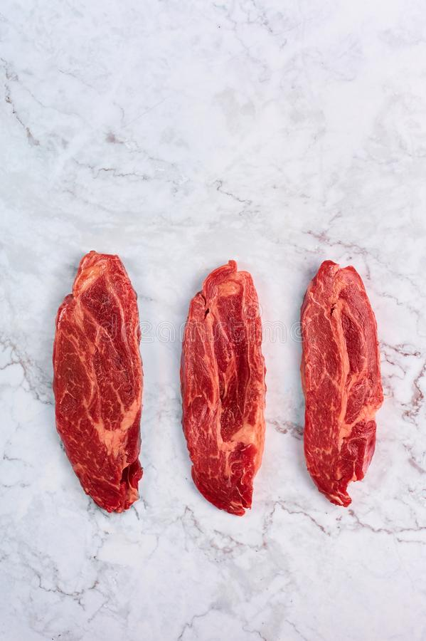 Raw marbled beef steaks at white marble background royalty free stock photo