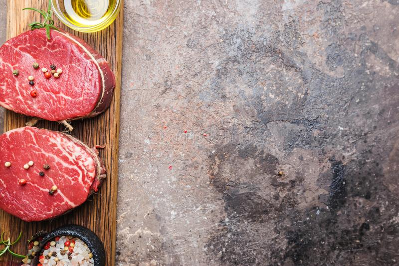 Raw marbled meat steak. Filet Mignon with seasonings over stone background, top view stock photography