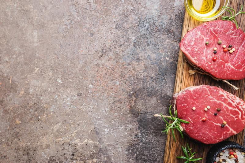 Raw marbled meat steak. Filet Mignon with seasonings over stone background, top view royalty free stock image
