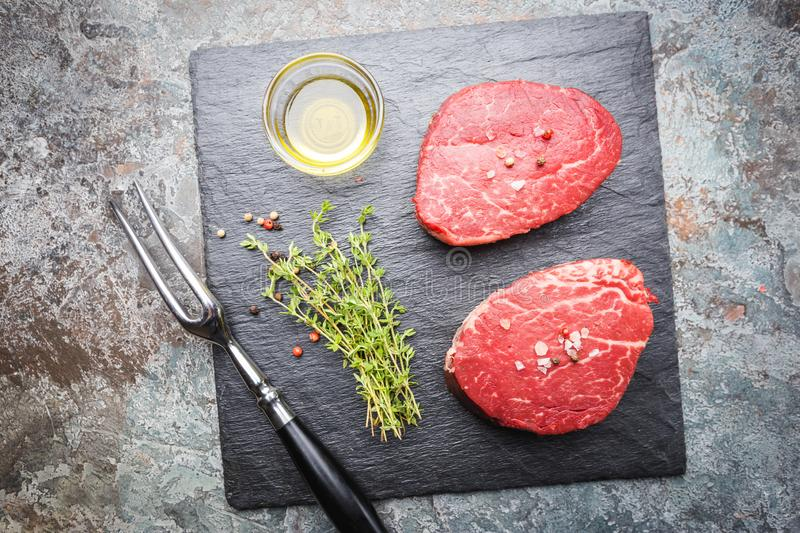 Raw marbled meat steak. Filet Mignon with seasonings over stone background, top view royalty free stock images